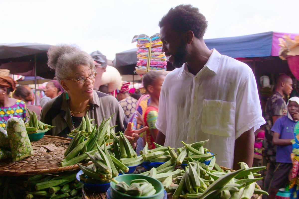 A man and a woman stand in front of an outdoor vegetable market in west africa