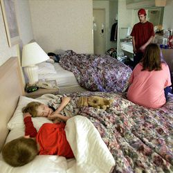 Cameron, 7, Dylan, 5, and Levi, 10, sleep in a hotel room provided by the American Red Cross as Connie and Russ Brown talk after he returned from salvaging items in their home.