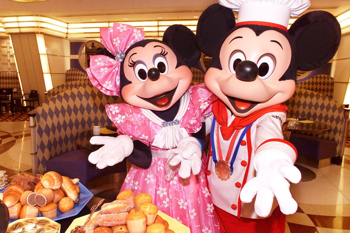 Mickey Mouse in chef's uniform, accompanied by Minnie Mouse, display a heap of breads on a plate during a press preview