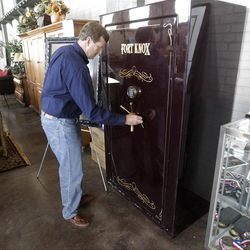 """This Oct. 17, 2012, photo shows Rulon Gardner's safe at the Erkelens& Olsen Auctioneers, in Salt Lake City. The auction of Olympic gold medalist Rulon Gardner's most valuable belongings is being postponed indefinitely as the decorated wrestler tries to buy back """"stuff that really matters to him,"""" his new bankruptcy lawyer says. A major creditor seized a Ford Excursion SUV, Harley-Davidson motorcycle, dozens of watches and knives, his wrestling shoes, autographed memorabilia and more. Gardner's gold and bronze medals are not in play; he previously put them up as collateral for personal loans. (AP Photo/Rick Bowmer)"""