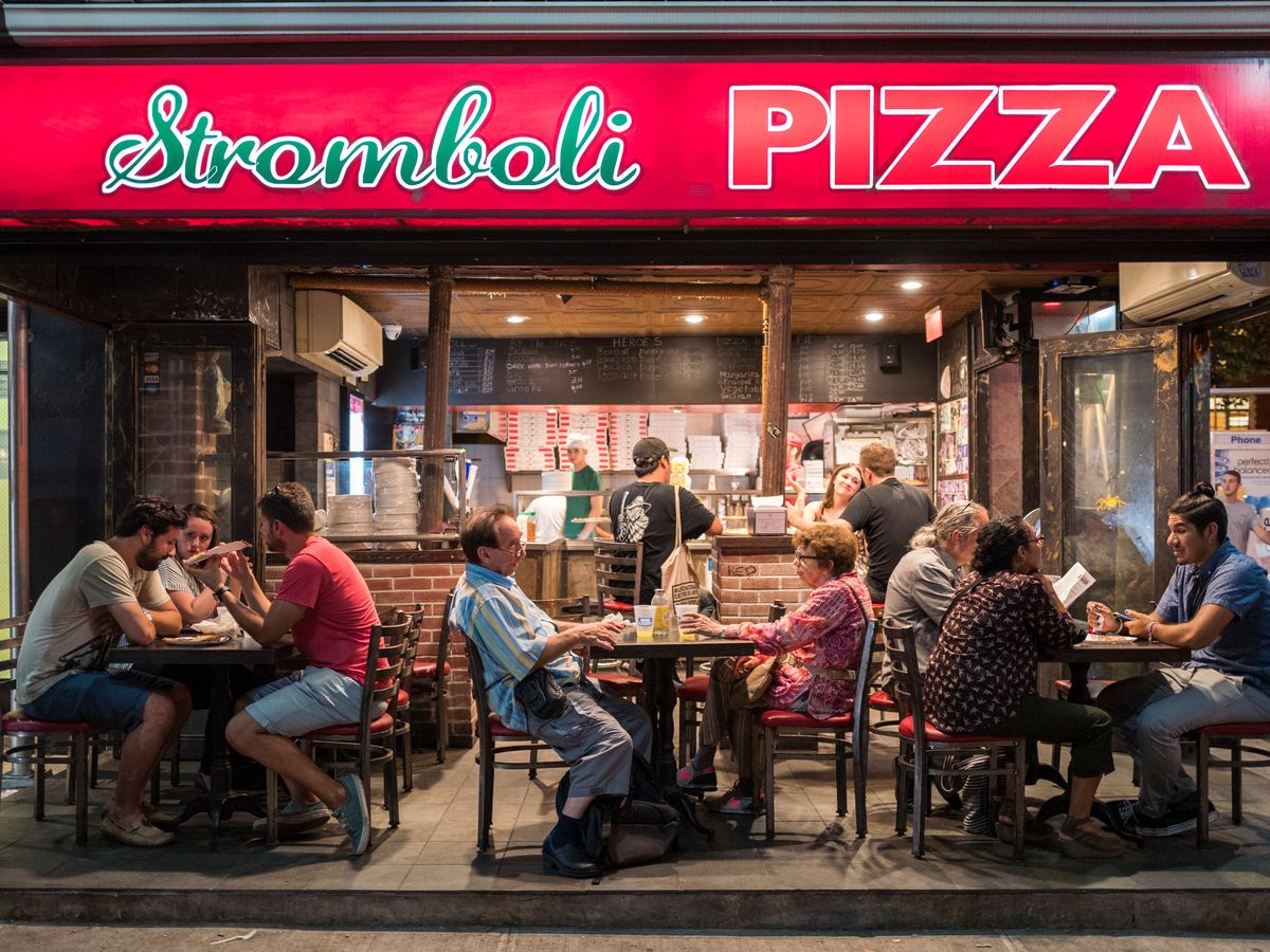 Diners sit at tables underneath the red StromboliPizza sign