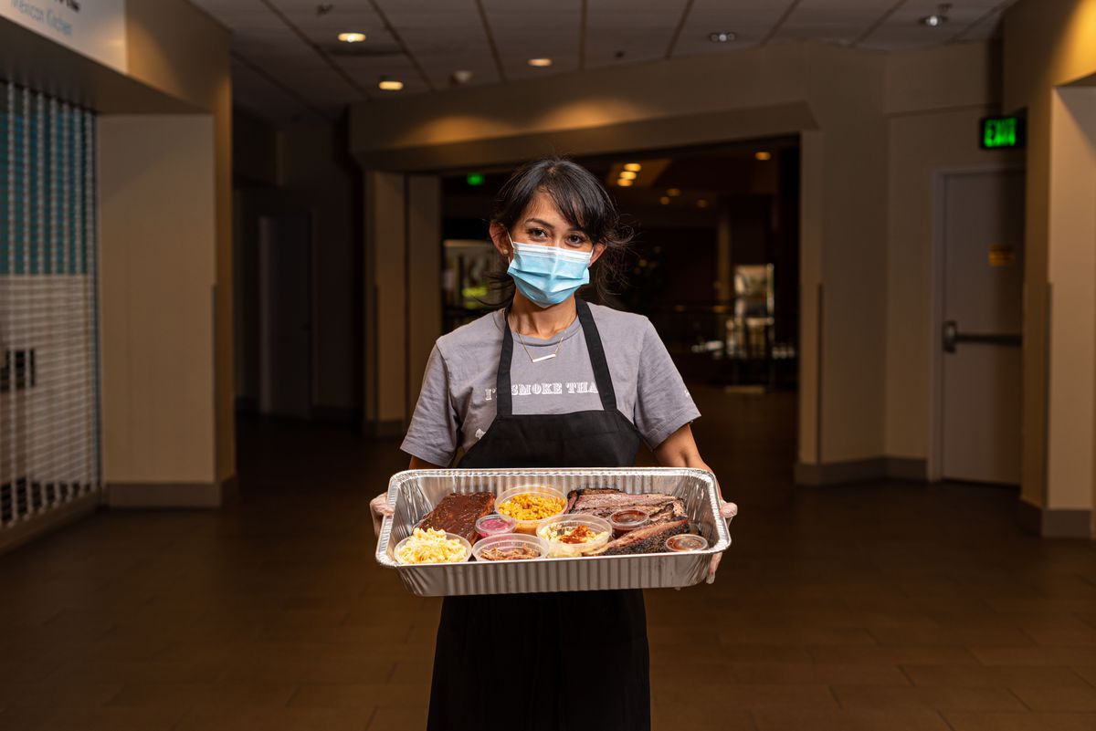 A woman in a blue mask holds a tray of barbecue inside of a darkened restaurant.