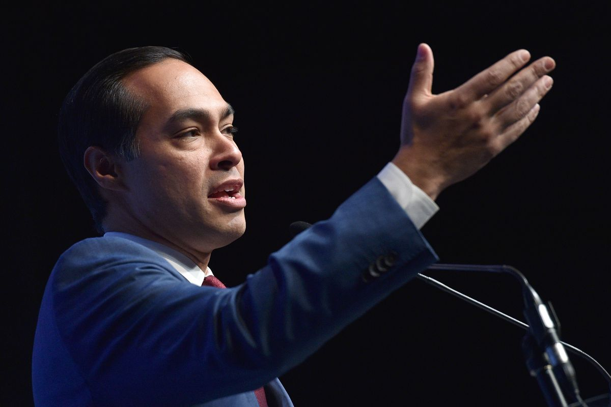 US presidential candidate Julián Castro speaks from a podium with one hand raised.