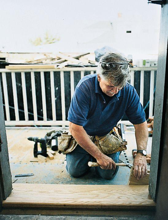 Man Installs Threshold In Exterior Door