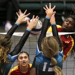 Mountain View middle blocker Mia Lee hits the ball over the net against Farmington outside hitter Hannah Howard (3) and middle blocker Alyssa Skabelund (13) during the 5A high school state finals match at the UCCU Center on the Utah Valley University campus in Orem on Saturday, Nov. 9, 2019.