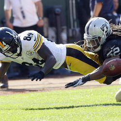 Pittsburgh Steelers wide receiver Antonio Brown, left, fumbles the ball near the goal line as Oakland Raiders linebacker Philip Wheeler, right, looks on during the third quarter of an NFL football game in Oakland, Calif., Sunday, Sept. 23, 2012. An unnecessary roughness penalty against the Raiders was called on the play giving the Steelers a touchdown.