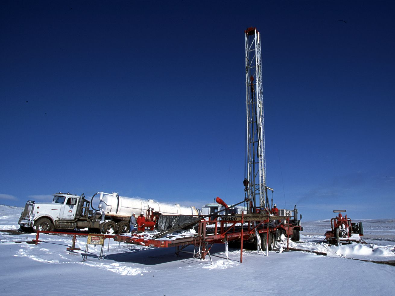 A mobile natural drilling rig in Gillette, Wyoming, sets up amid snow. Extreme cold this week has increased natural gas demand, so some utilities have asked customers to lower their heat.