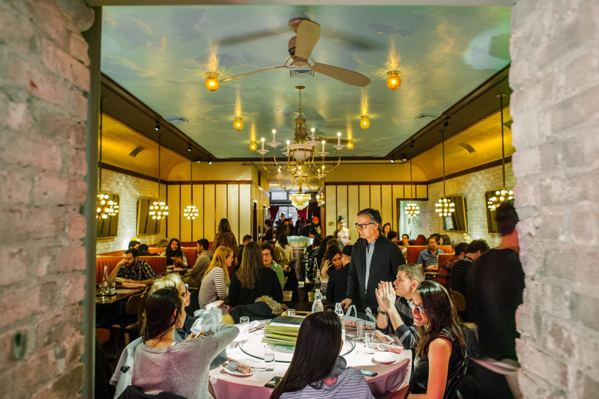 Customers sitting and standing inside Mission Chinese's bustling dining room