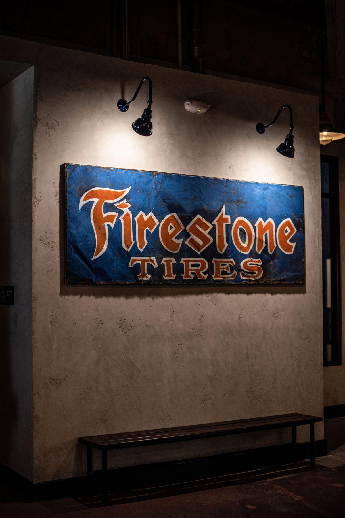 A dark blue banner reads Firestone Tires under low light.
