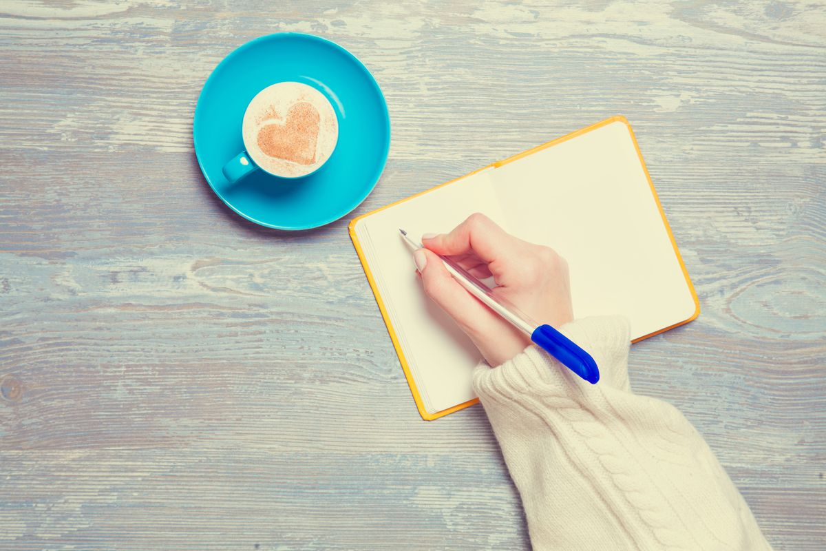 A hand scribbles in a notebook next to a delicious cup of coffee.