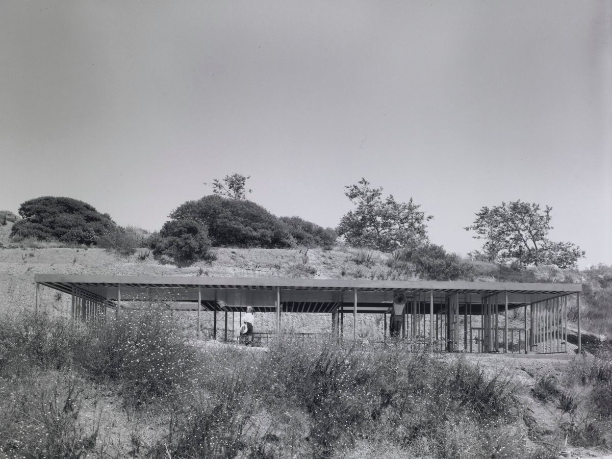 A simple, rectangular house with a long flat roof under construction.