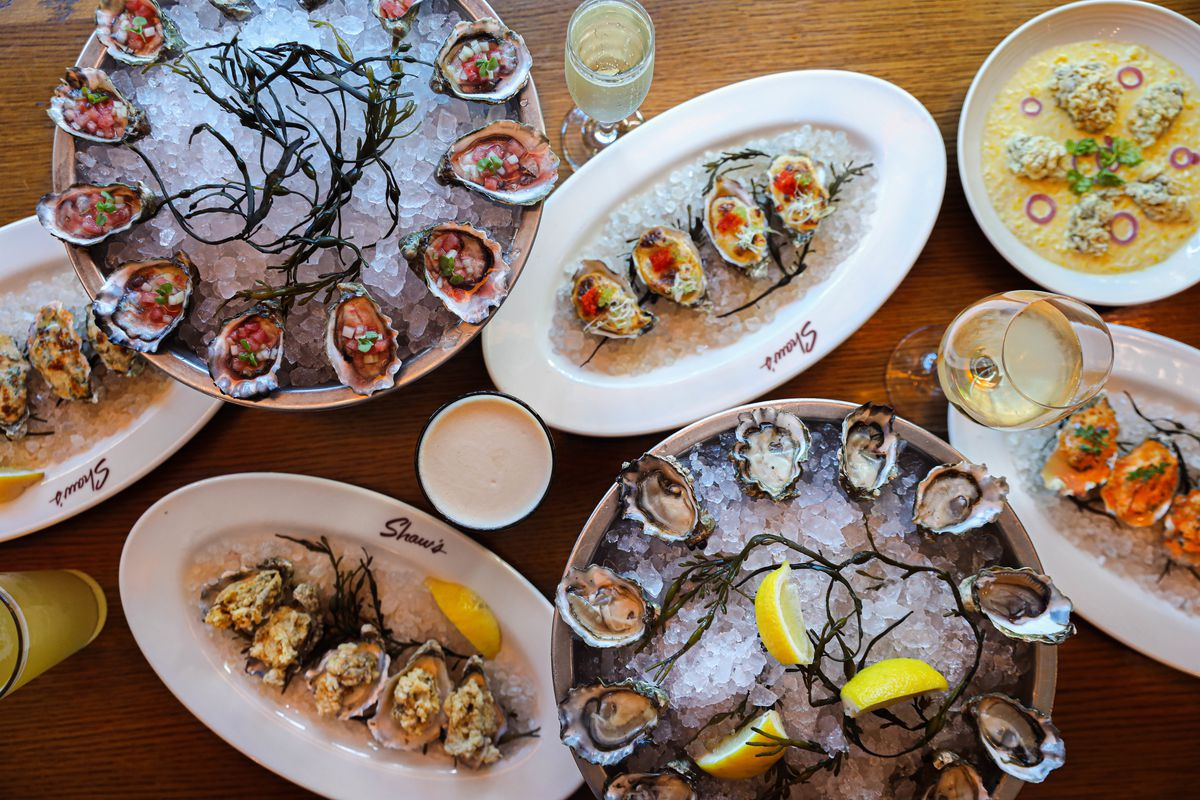 A table piled with plates containing oysters.
