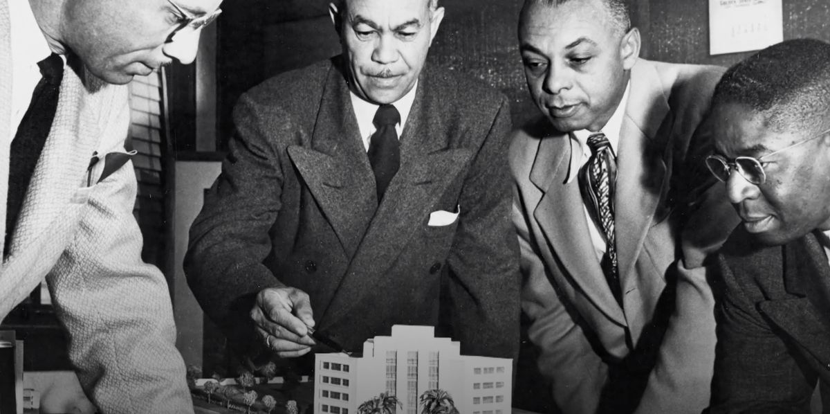 Four men hovering over a small architectural model.