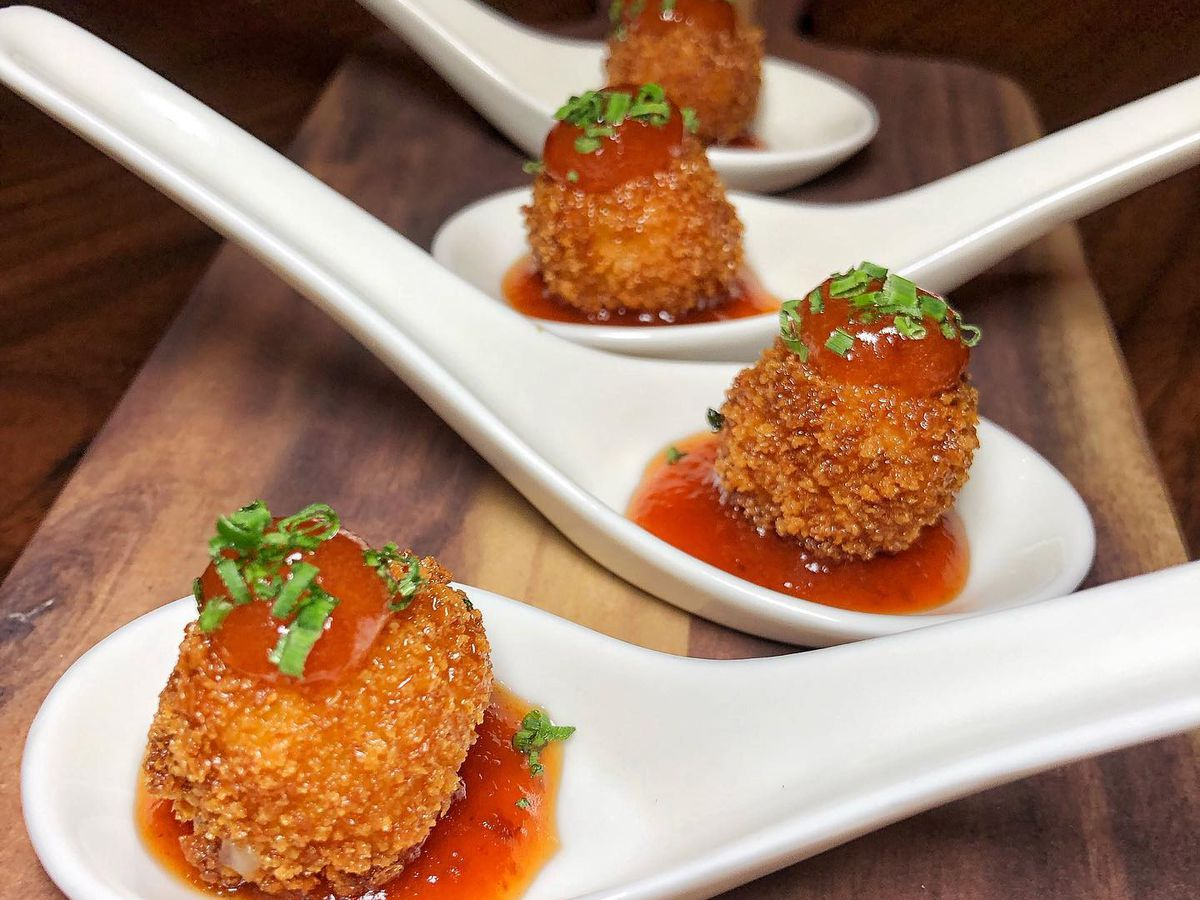 Spoons De La Mancha with fried manchego cheese with tomato jam, spicy honey, and membrillo sauce served on spoons at Boteco