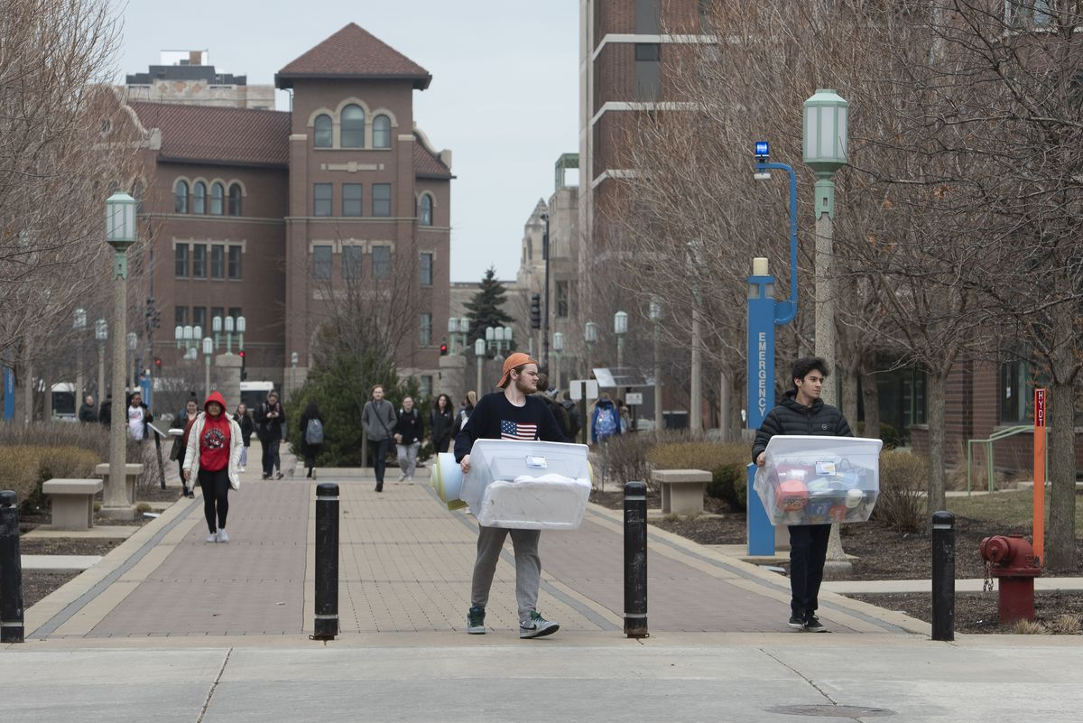 Students carry personal belongings as they moved out of the dorms at Loyola University in March, when the school had to shut down suddenly because of the coronavirus.