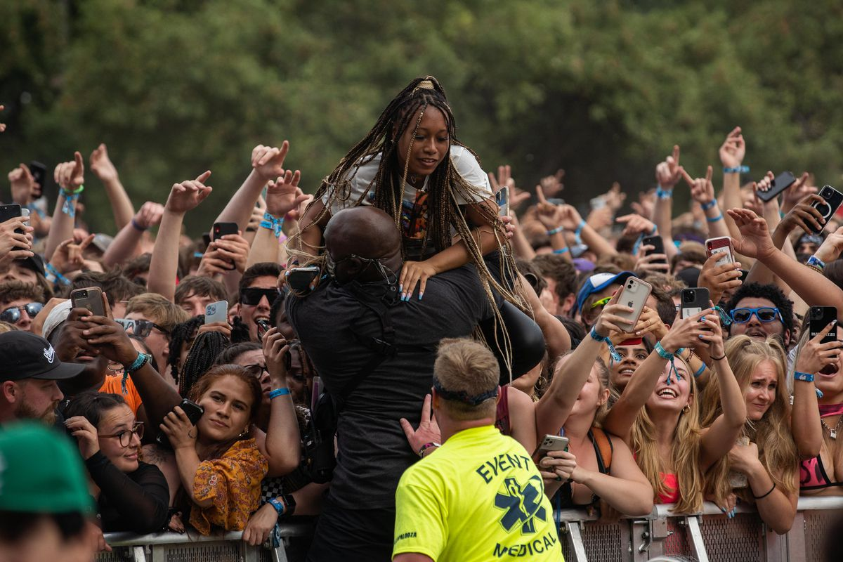 A festival goer is carried out of the crowd during Polo G's show.