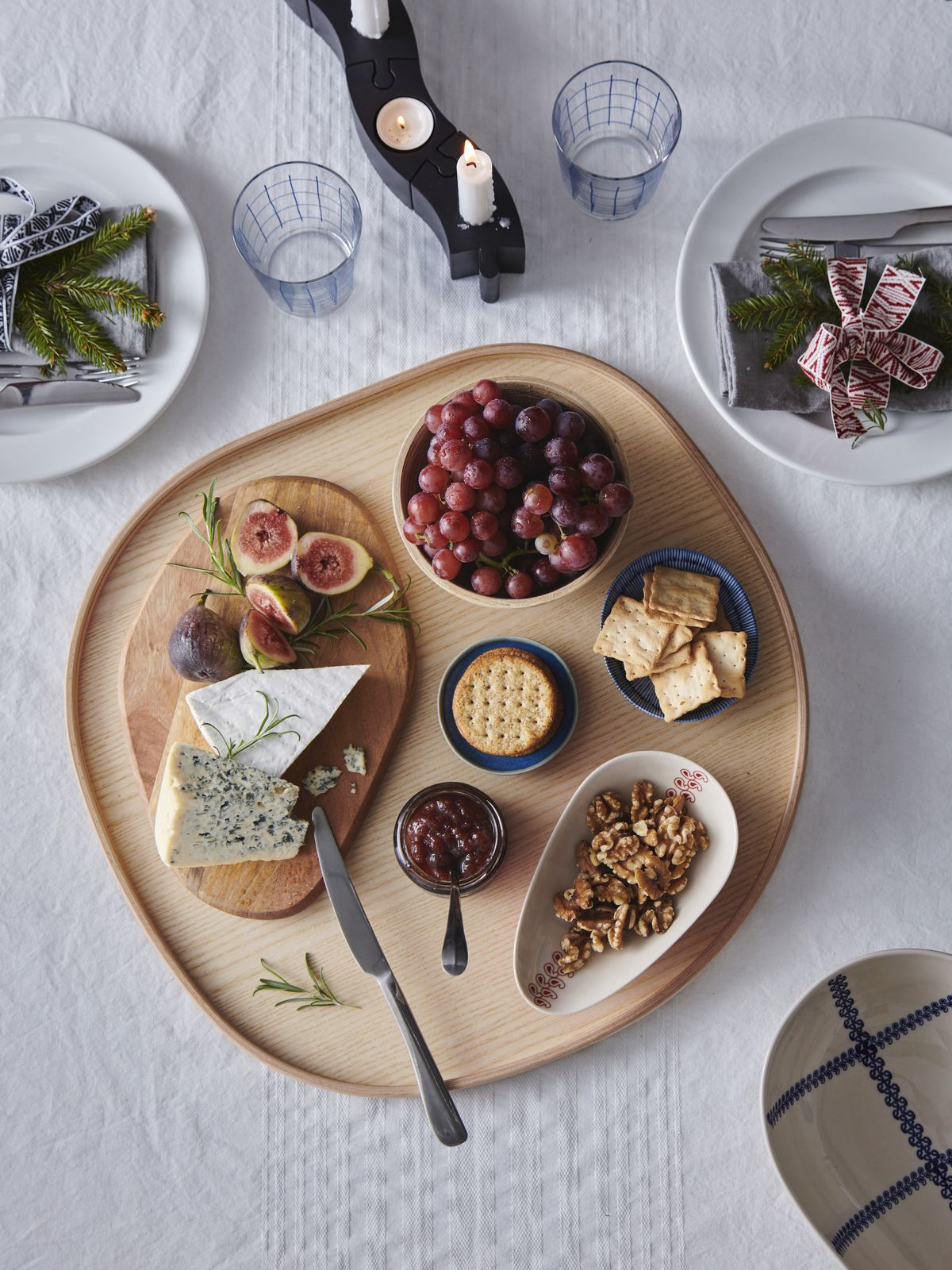 An overhead shot of a wooden serving tray containing a smaller board of cheese, and small dishes holding grapes, nuts, and crackers.