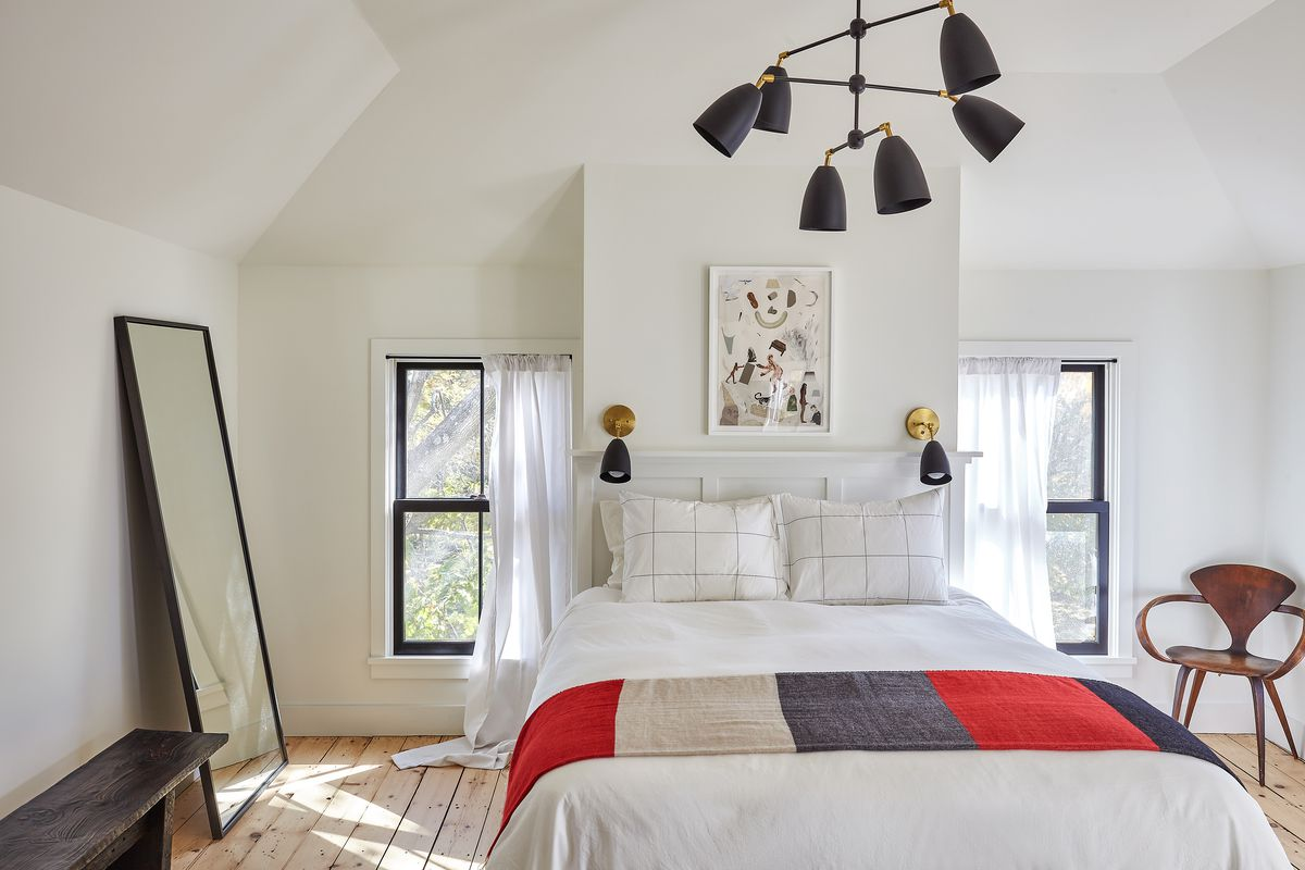 A white room containing a bed with a striped blanket, a mirror leaning against a wall, and an antique chair in the corner.