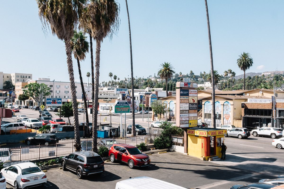 An aerial view of a major Los Angeles thoroughfare lined with strip malls and a motel. Hills in the background.