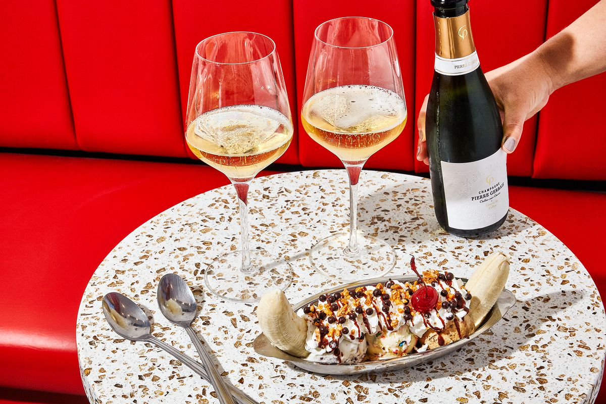 A banana split drizzled with chocolate and topped with a cherry sits on a table alongside two spoons and two glasses of champagne, against a backdrop of red banquette seating