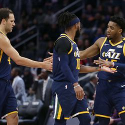 Utah Jazz guard Donovan Mitchell, right, celebrates with forward Bojan Bogdanovic, left, and guard Mike Conley during the first half of the team's NBA basketball game against the Detroit Pistons on Saturday, March 7, 2020, in Detroit. The Jazz won 111-105.