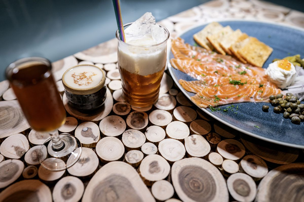 Beer, cocktails, and a plate of cured salmon with capers