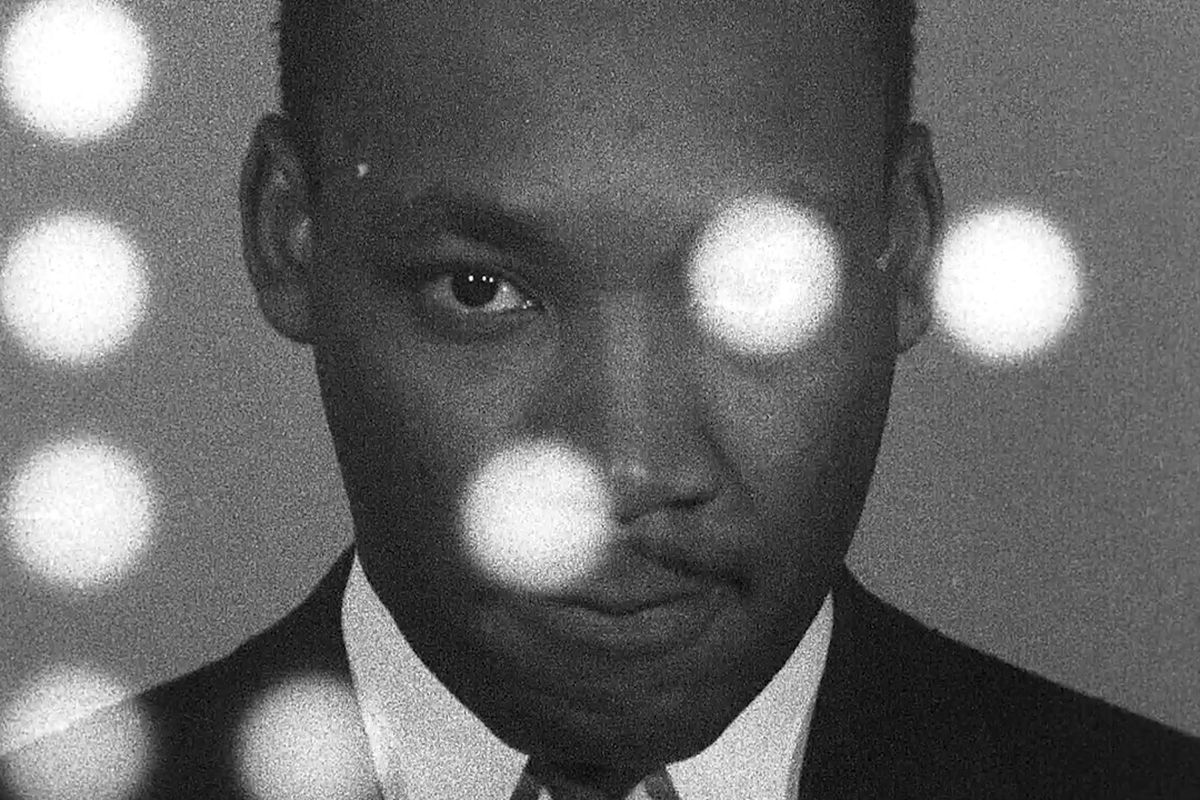 Dr. Martin Luther King Jr. looks at the camera, with points of light obscuring parts of his face.