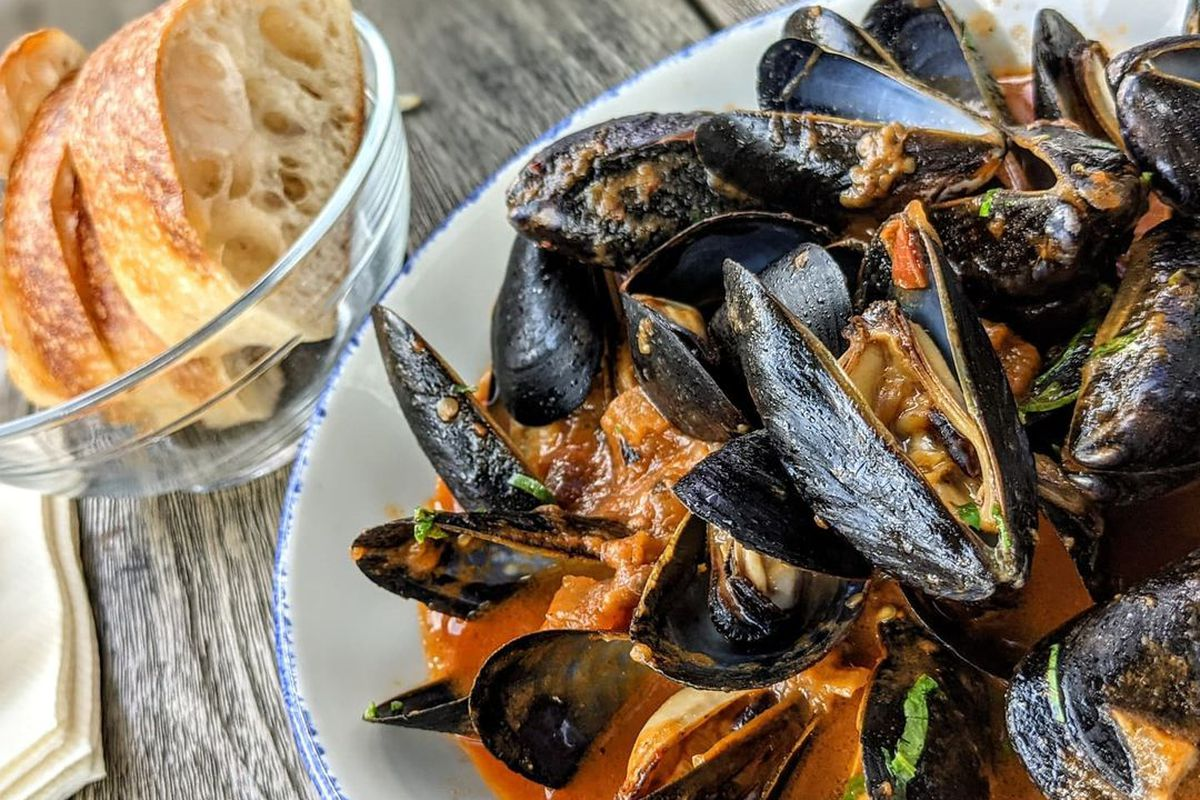 Mussels in a thin red broth fill a white plate, which sits on a table with an aged faux-wood surface. A small glass bowl of sliced bread sits next to the mussels.