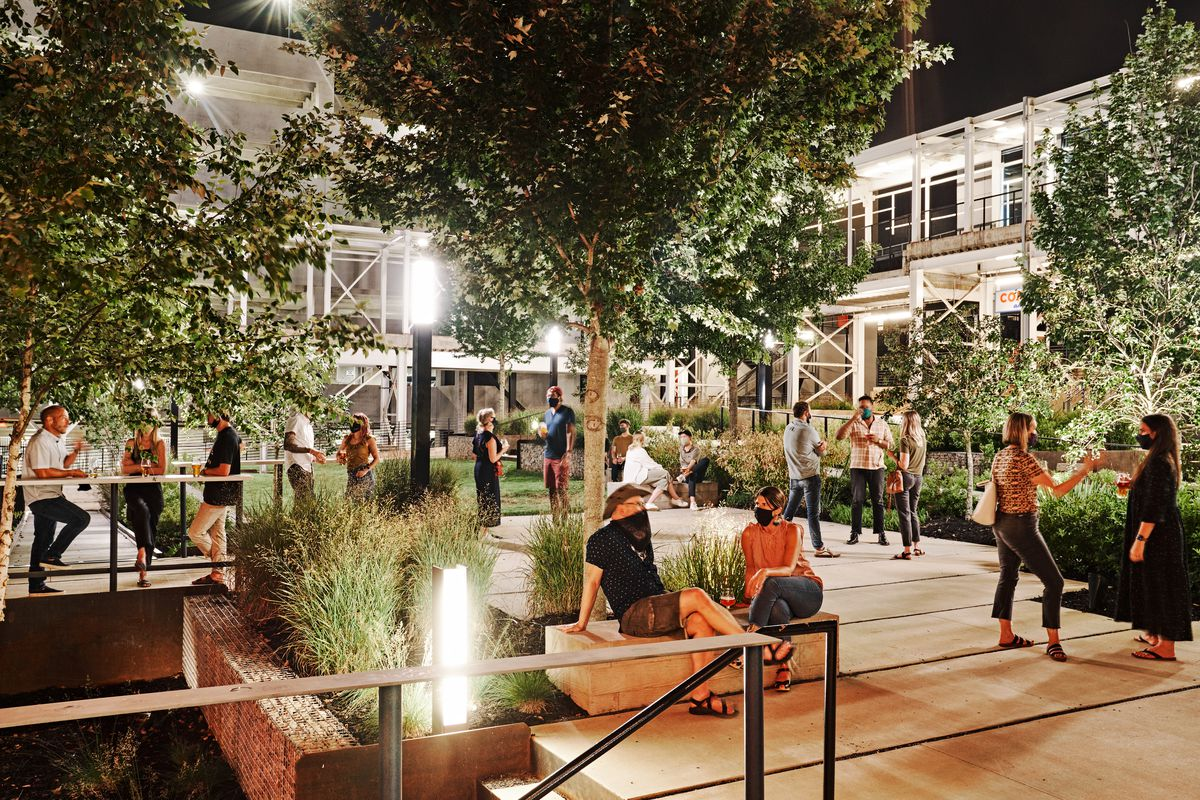 A shot of the Yard greenspace lit up at night with masked people standing around talking and drinking beer at Atlanta Dairies