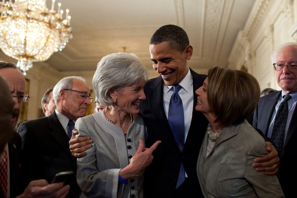President Obama hugs HHS Secretary Kathleen Sebelius and House Minority Leader Nancy Pelosi.