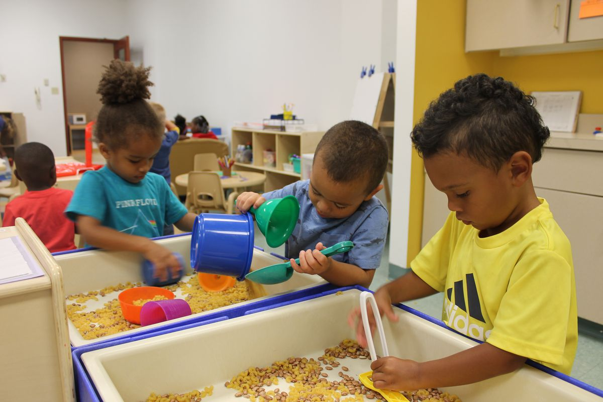 Preschool students play with beans and dried pasta at a sensory center in a preschool classroom at Day Early Learning at Eastern Star Church.