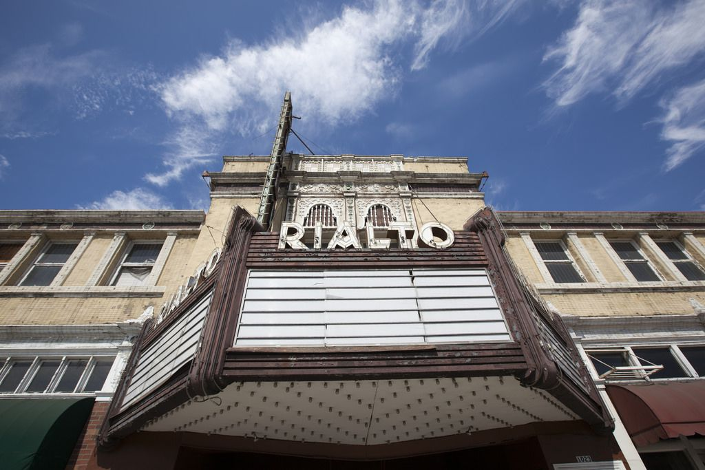 The exterior of a theater. There is a theater marquee and the sign above it reads Rialto.