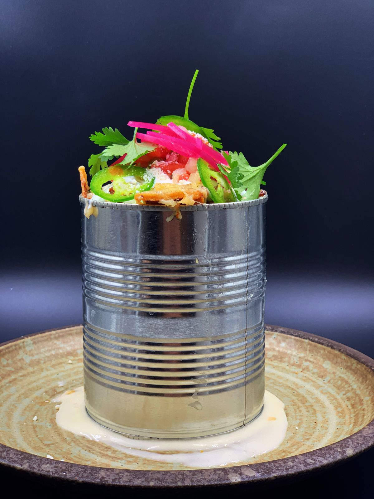A metal can sits on a plate, with cilantro, red onions, jalapenos, and other ingredients rising out of the top