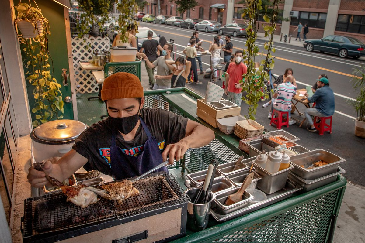 A person in an orange beanie handles pieces of chicken at a tabletop grill. In the background, diners sit at tables and wait to order food.