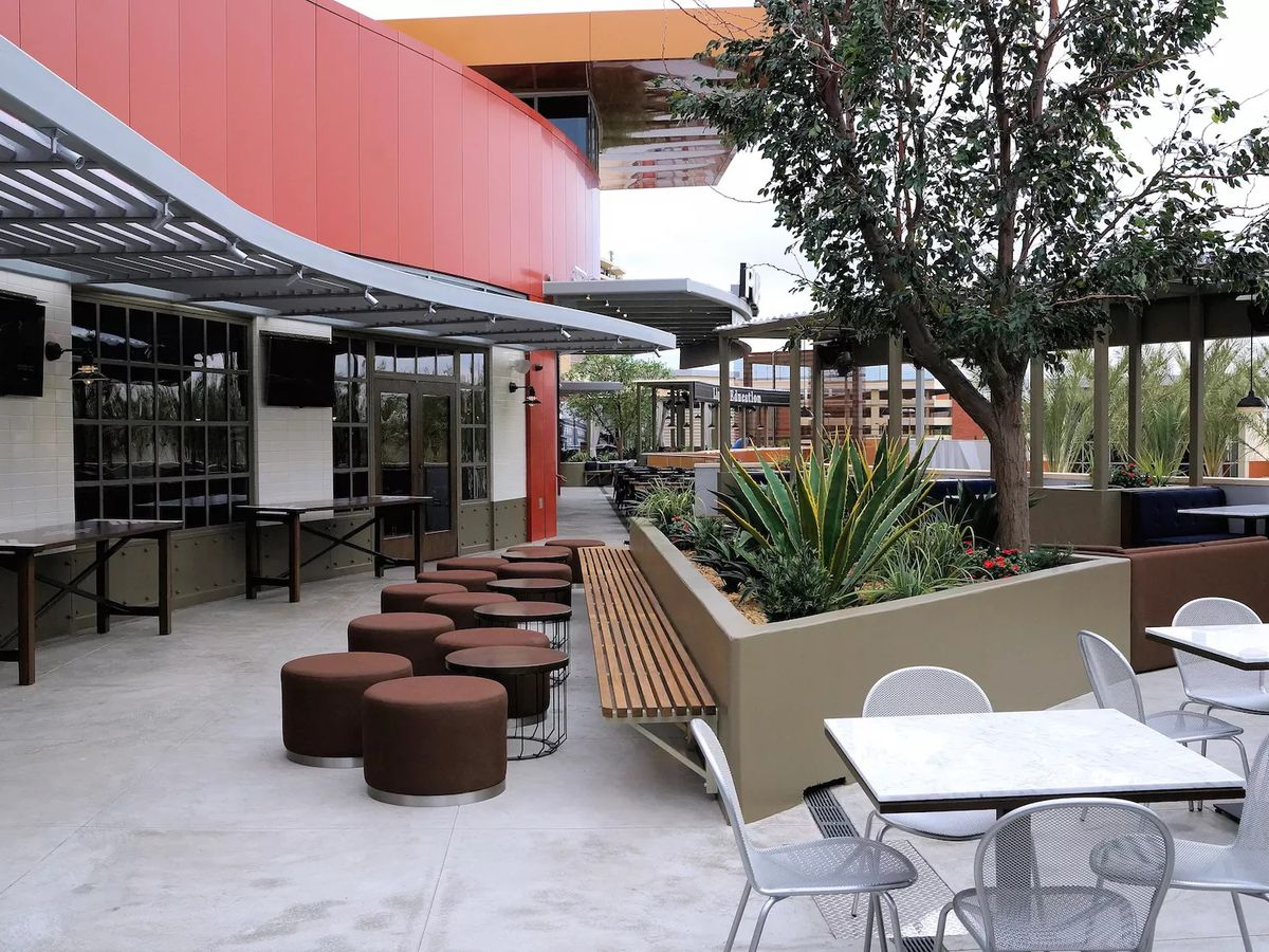 A patio with metal chairs and white tables