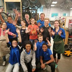 A group of volunteers and children pose for a picture at the Ogden Bicycle Collective.