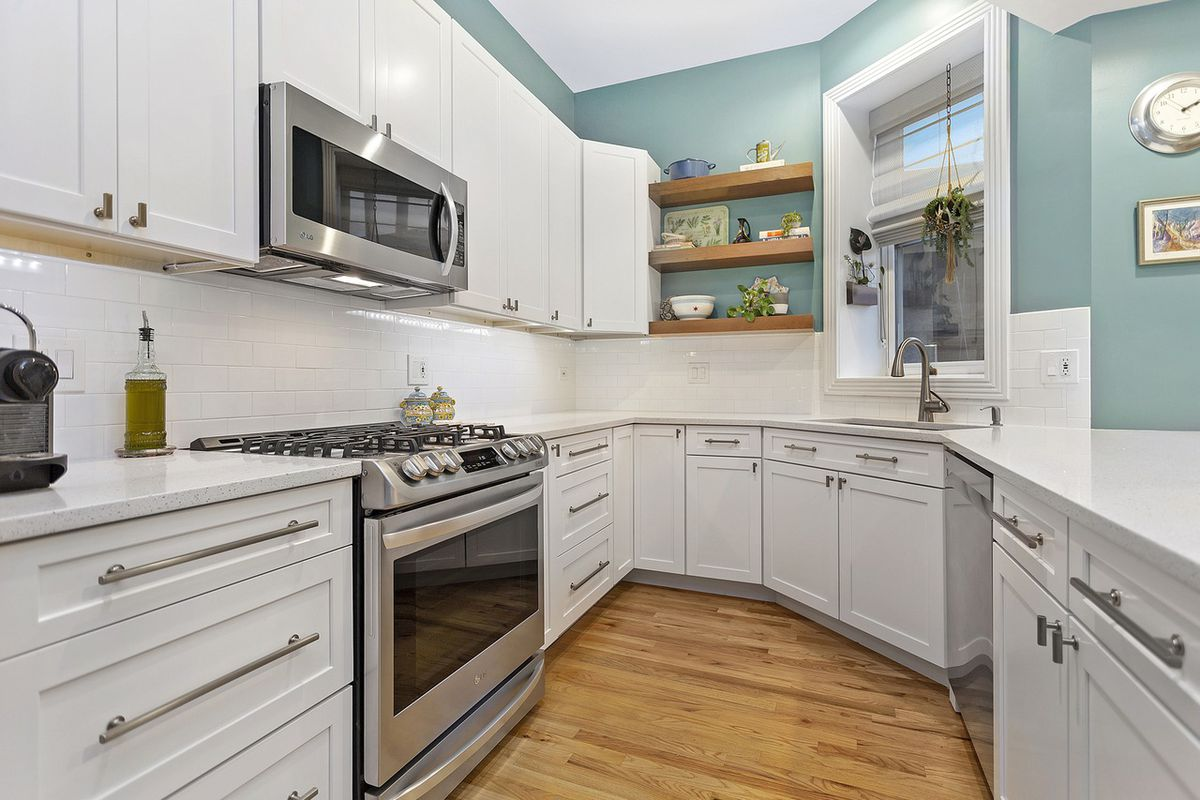 White cabinets, metal appliances, and single window line this kitchen space.