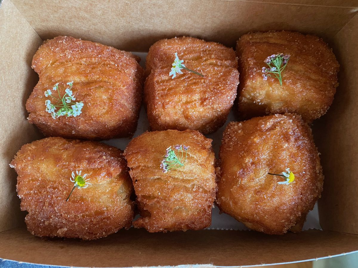 Six square, light brown donuts in a cardboard takeout container, with a small sprig of microflowers placed on the top of each donut