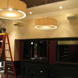 The main dining room features large drum lights, mirrors and splashes of burgundy.