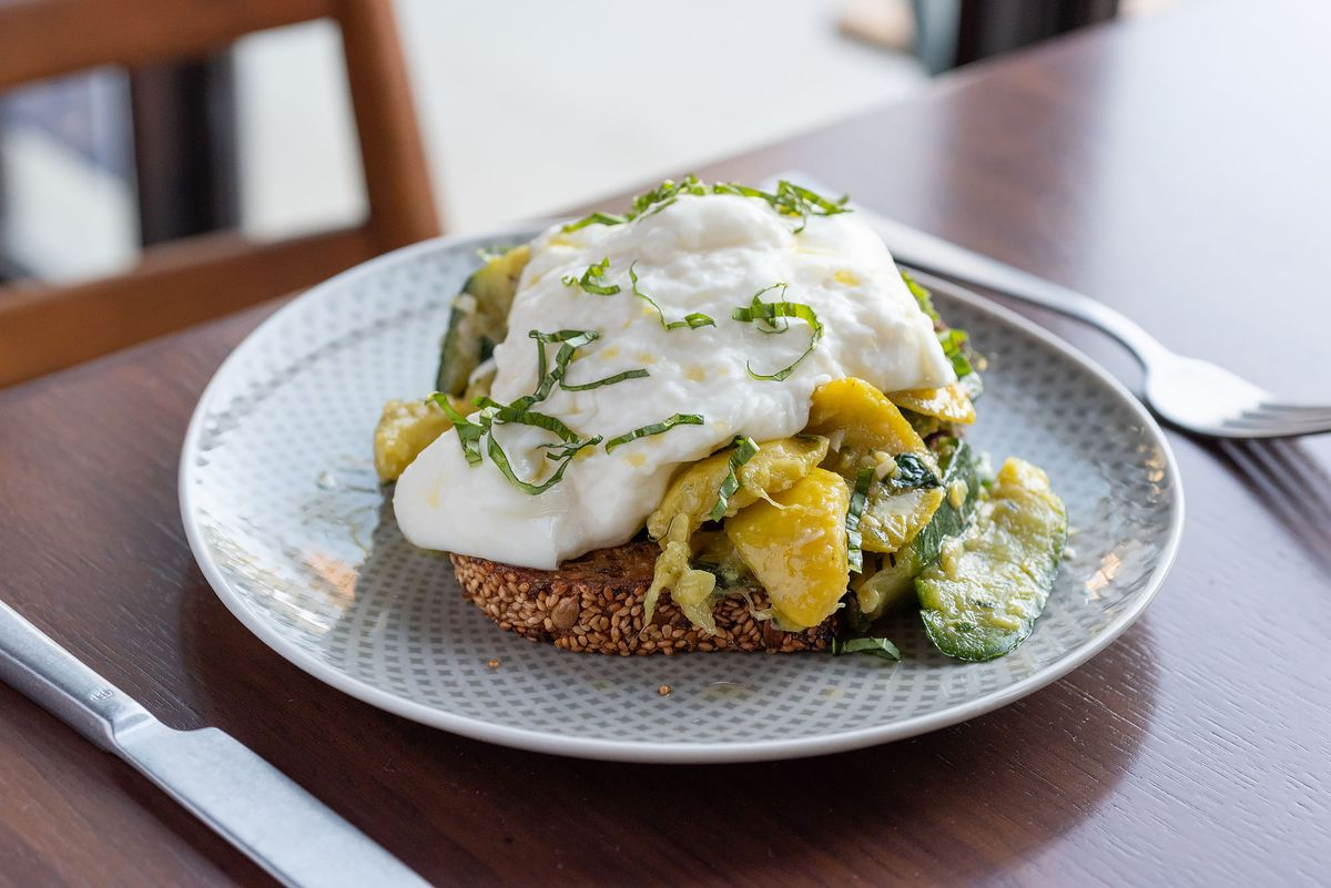 A burrata and squash-covered toast on a rippled white plate.