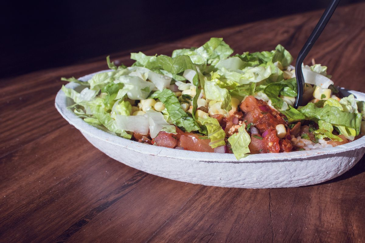 Molded fiber bowl filled with burrito bowl ingredients: lettuce, tomatoes, corn, rice, etc.