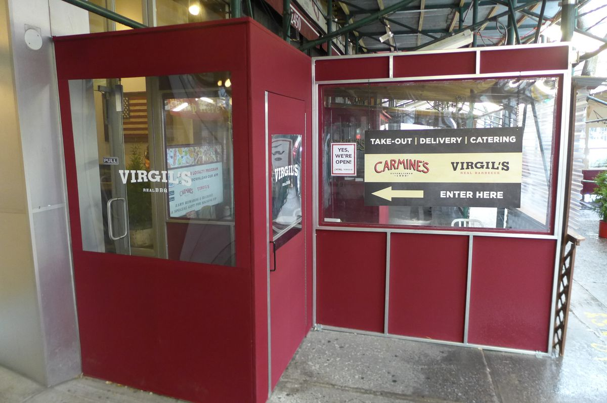 A red entrance canvas outdoor cubicle with Virgil's and Carmine's printed on it.