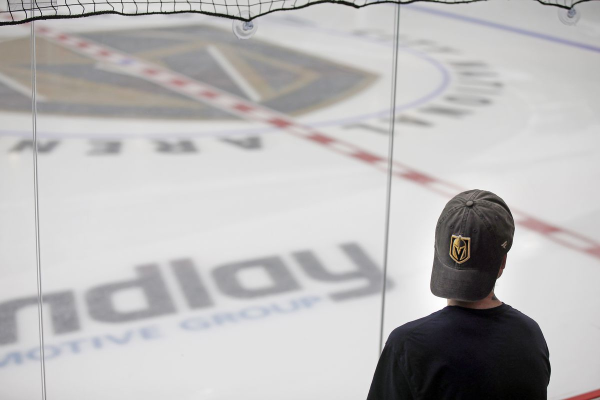 Man in backwards Golden Knights baseball hat looks onto the ice