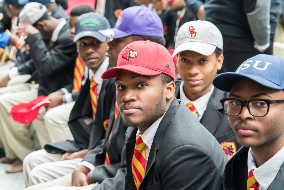 Urban Prep students in their uniforms — including seniors' signature striped ties — and college baseball caps on Signing Day last year.