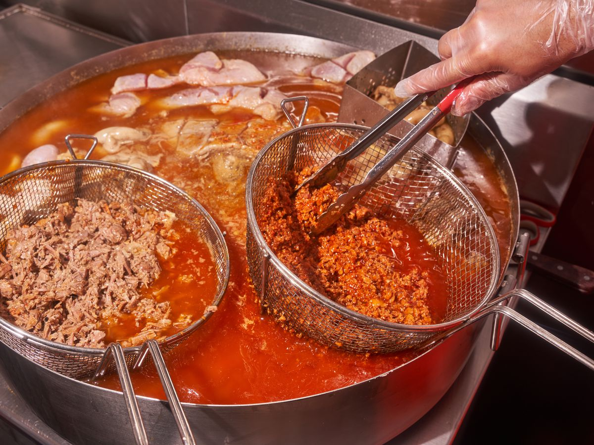 A gloved hands hold a sieve of crumbly red meat over a vat of orange fat and oil, also filled with other meats