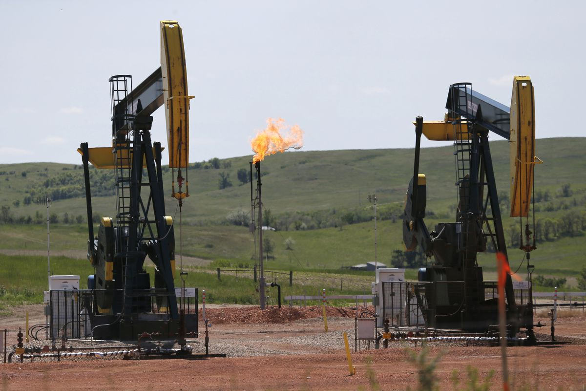 In this June 12, 2014, file photo, oil pumps and natural gas burn off in Watford City, N.D. The Interior Department is delaying an Obama-era regulation aimed at restricting harmful methane emissions from oil and gas production on federal lands.