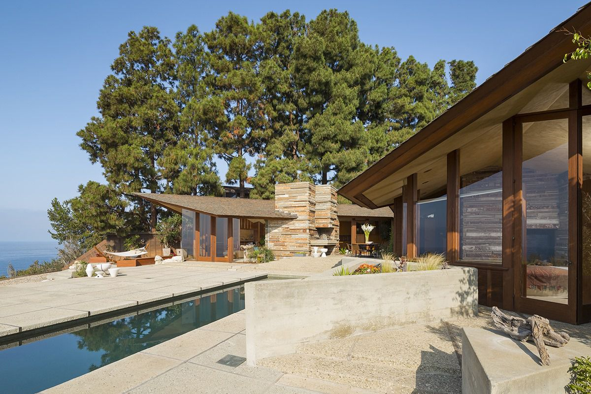 Exterior shot of a midcentury modern house with floor-to-ceiling windows framed in redwood and and a cantilevered roof.