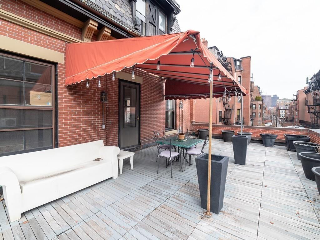 A second-floor roof deck with an awning over the door leading on to it. There's a couch.