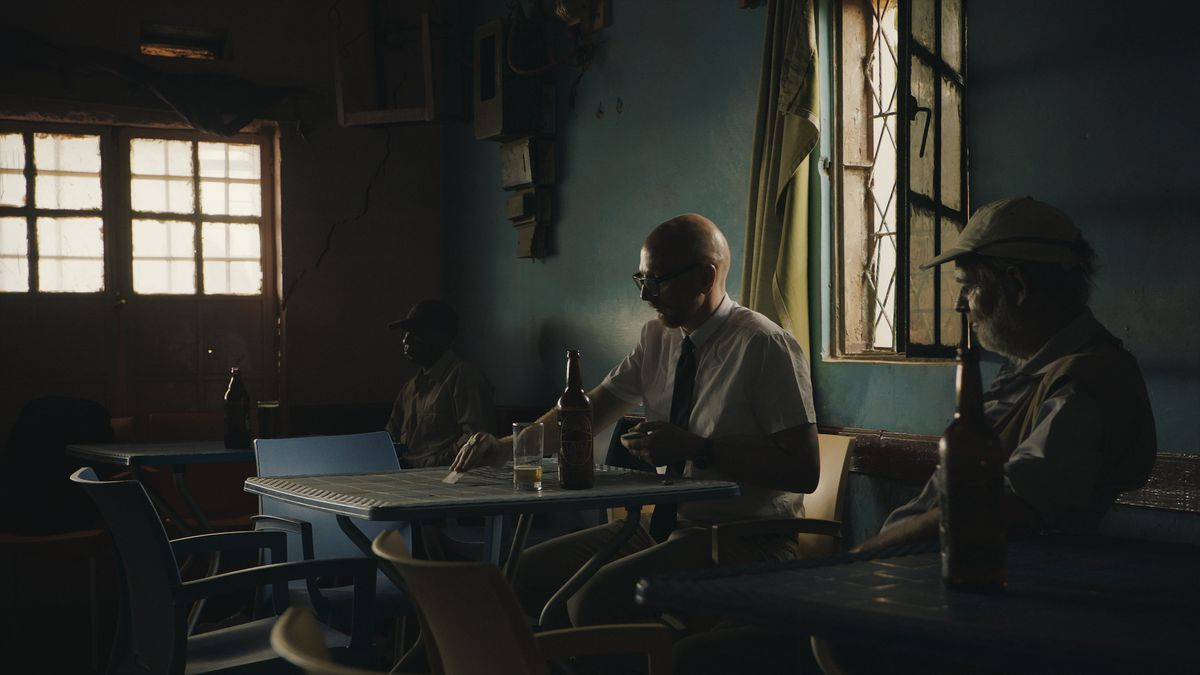 Documentarian Mads Brugger plays solitaire while drinking a beer in a shadowy bar in a scene from Cold Case Hammarskjold