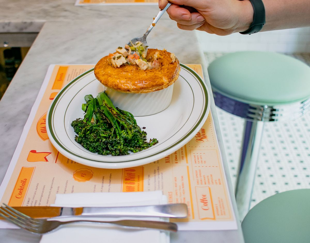 A person digs a spoon into the pastry top on a chicken pot pie, revealing chicken, carrots, and peas inside. Green broccoli lays on the side of the white plate with the pot pie.